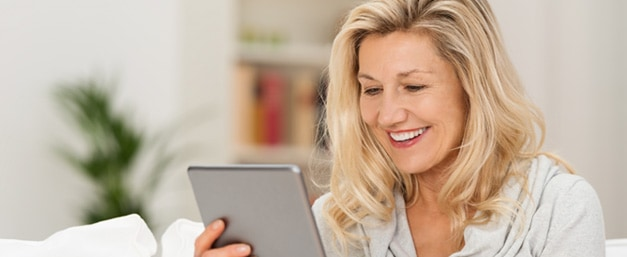 middle aged woman on tablet without readers