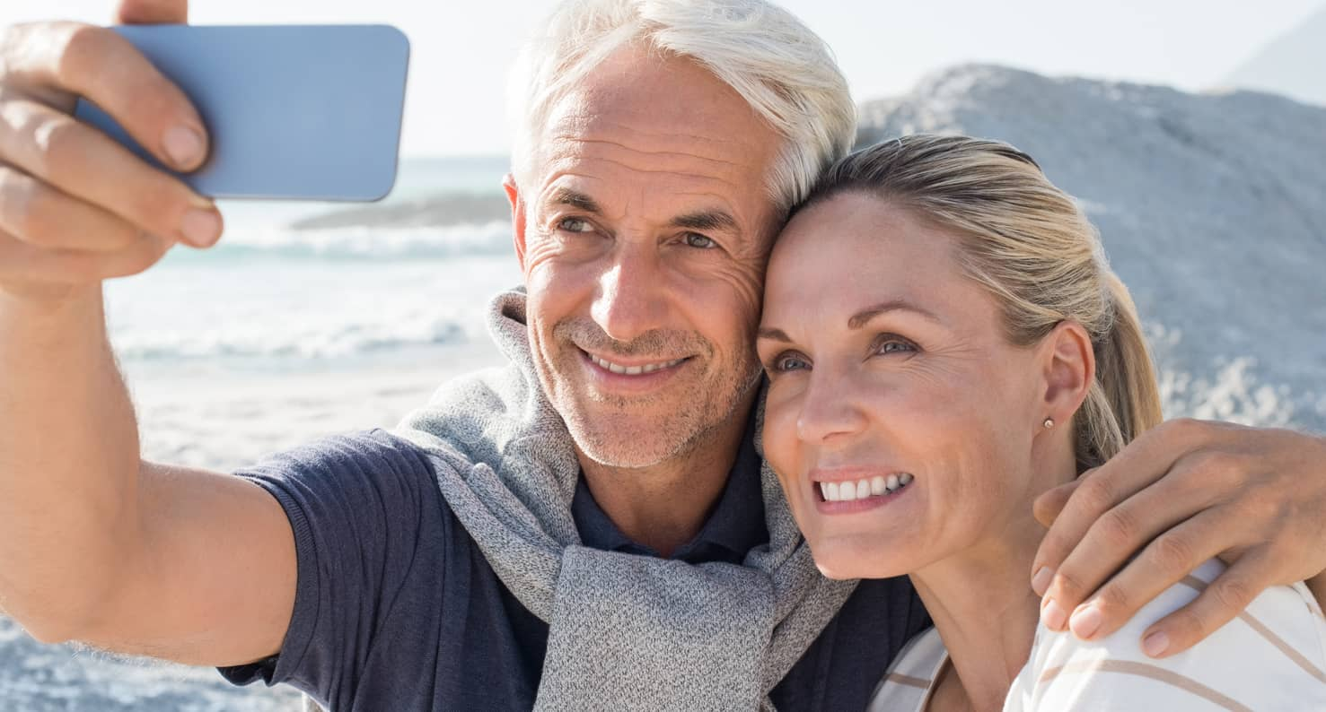 older couple taking a selfie by the ocean