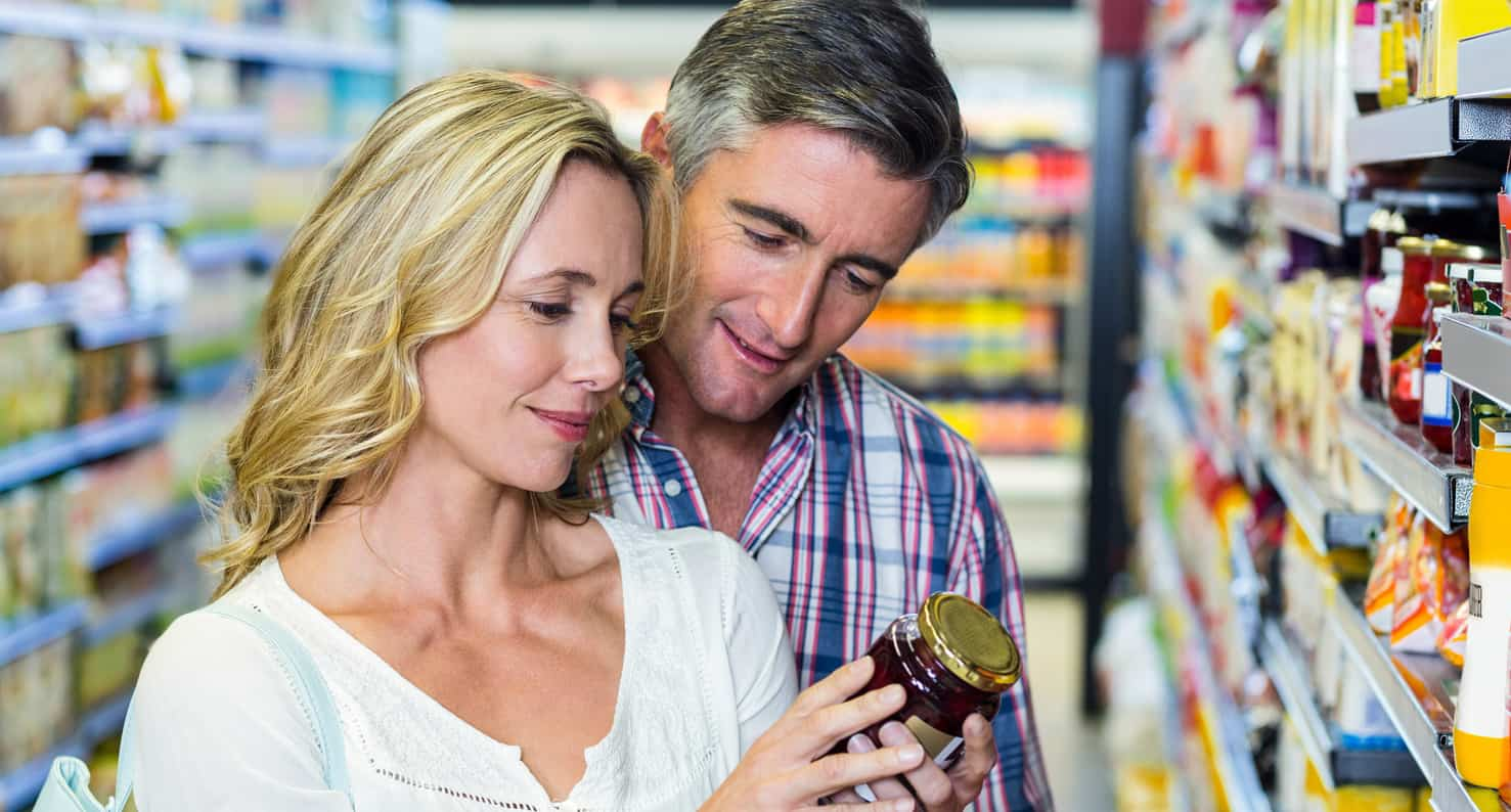 middle aged couple reading jar at grocery store