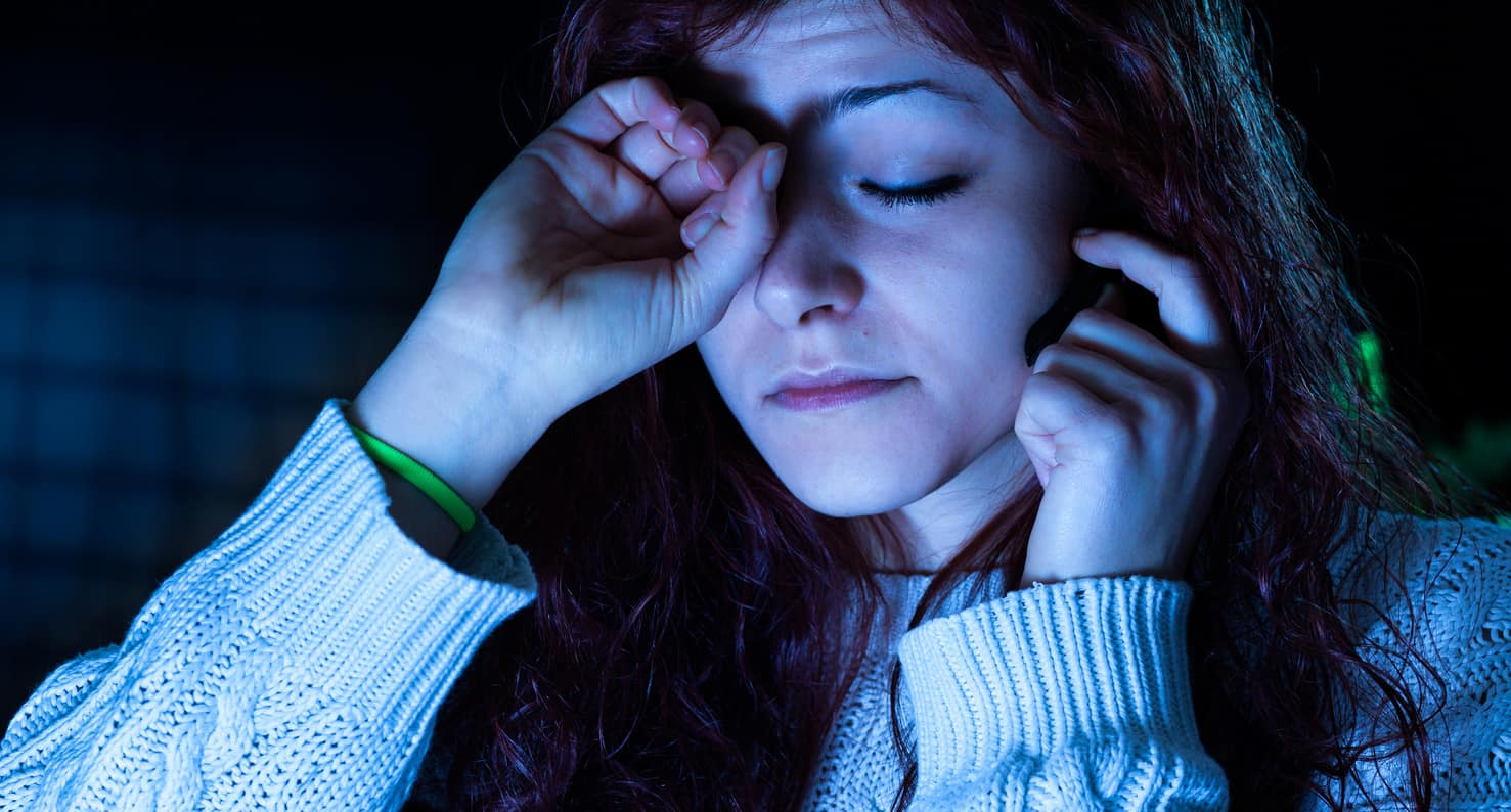 young woman rubbing eyes