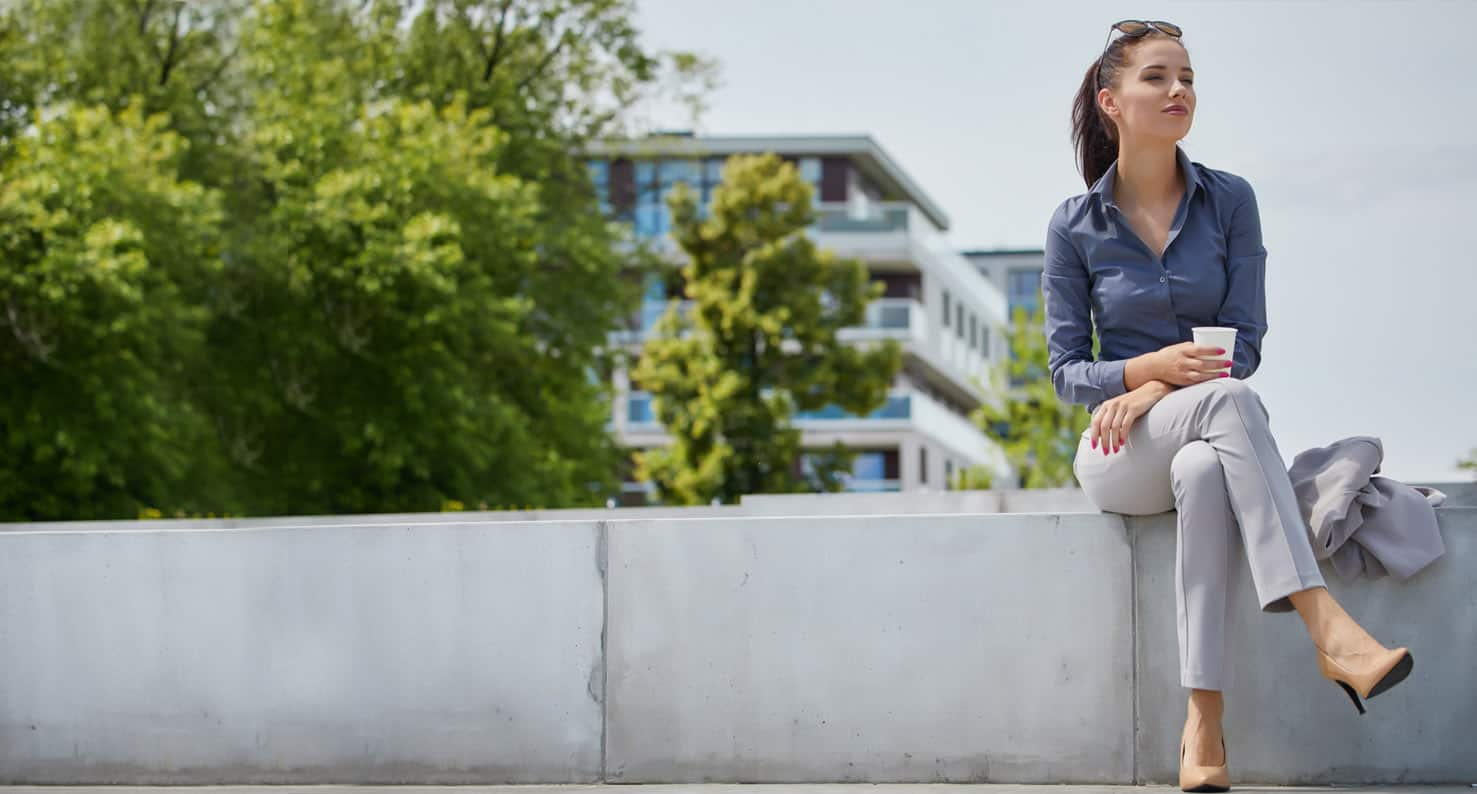 A business woman enjoys coffee outside on her lunch break.