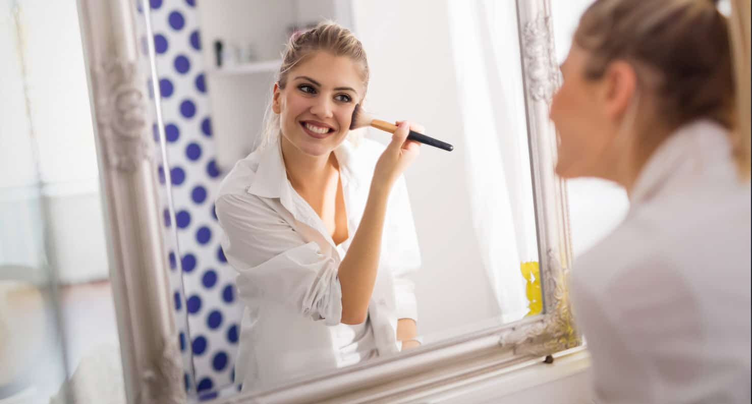 A happy woman applying makeup in her bathroom mirror.