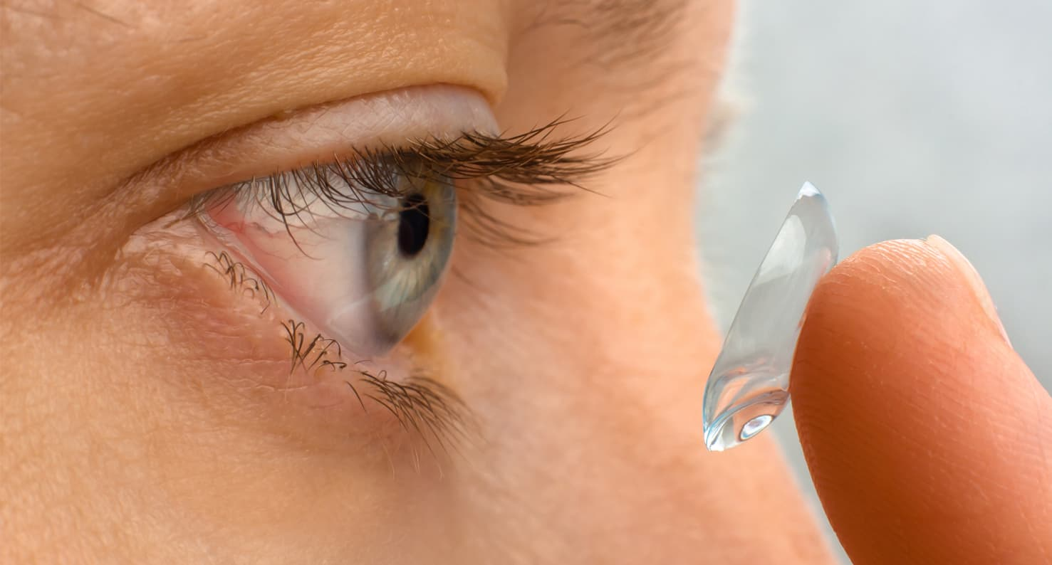 Closeup of person putting contact into red, irritated eye.