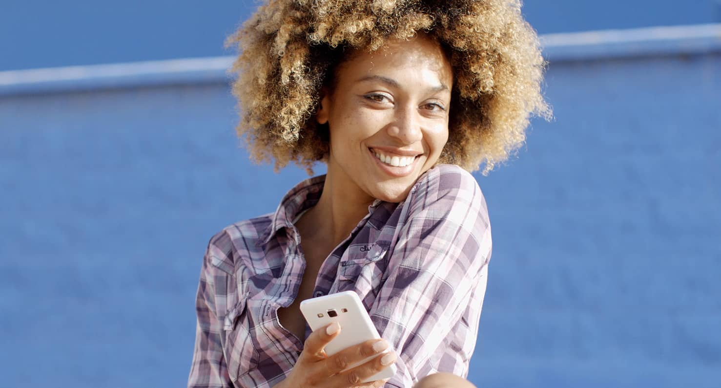 Happy woman in a flannel shirt smiling at camera and holding a iphone.