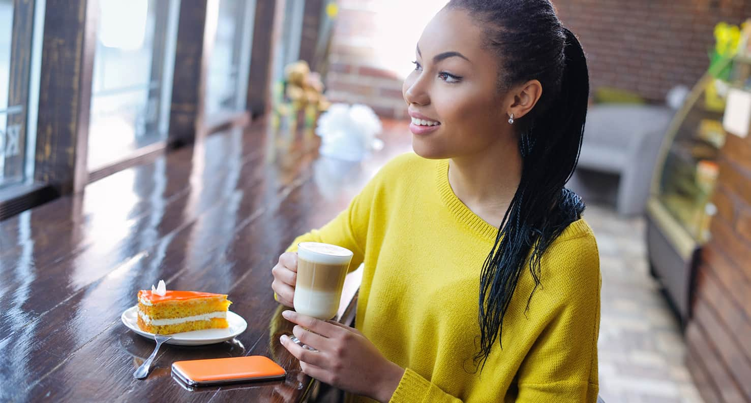 Smiling woman in yellow sweater at cafe.