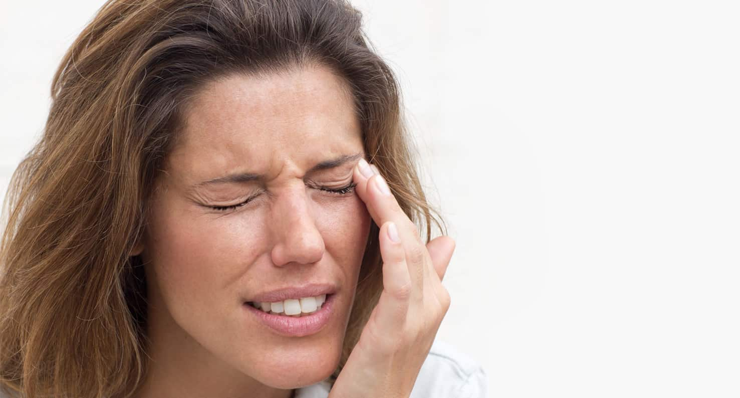 Woman looks uncomfortable and is rubbing dry eye