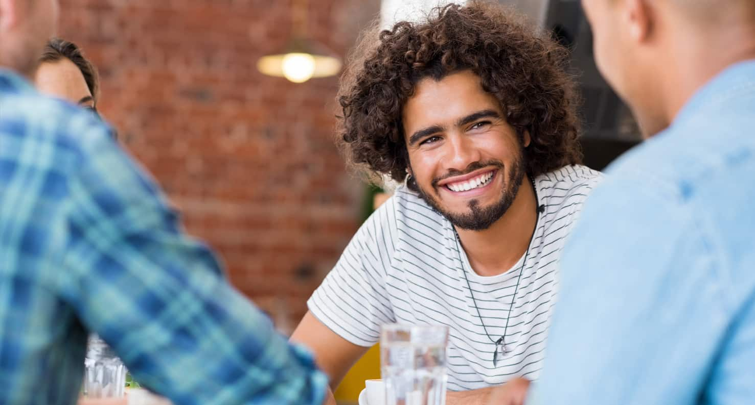 Smiling young man with curly hair, chatting with friends in a coffee house.