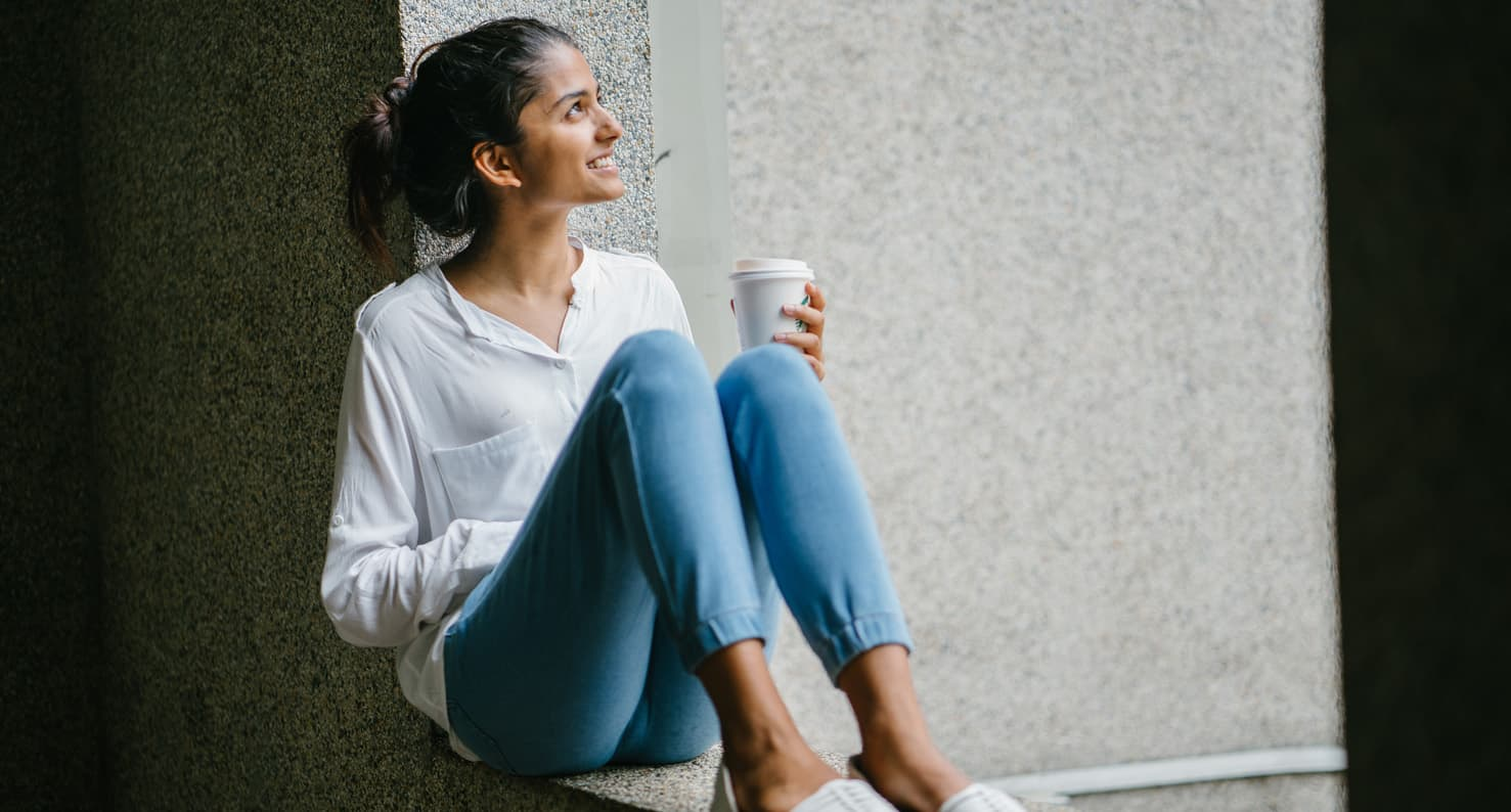 young adult woman drinking coffee outside