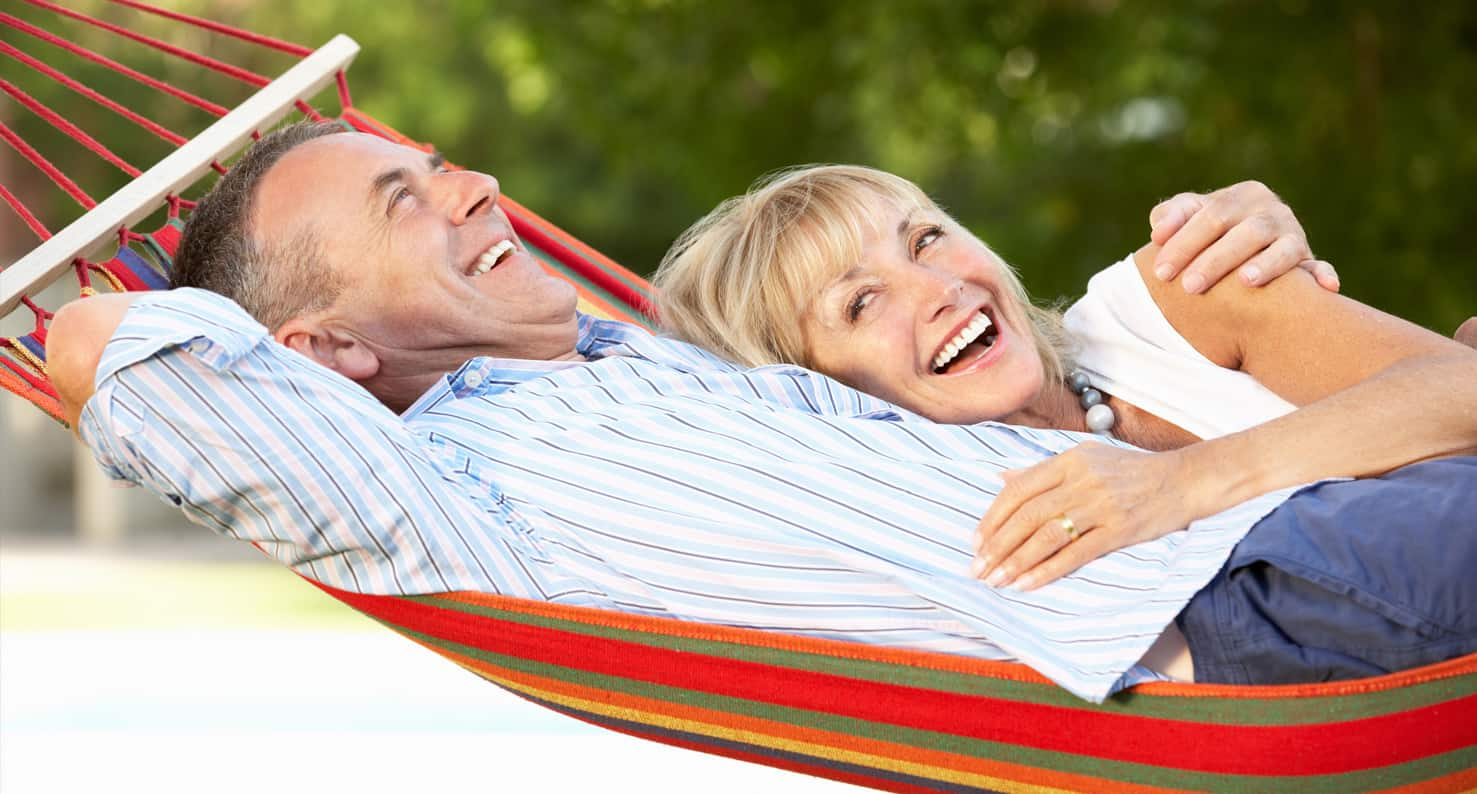 A happy couple relaxes and laughs together while laying in a hammock.