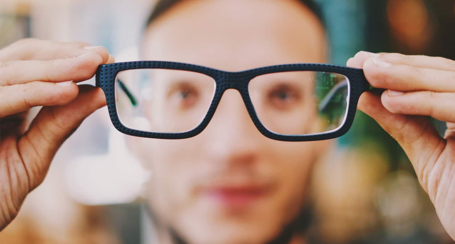 A man with astigmatism holds out his thick glasses