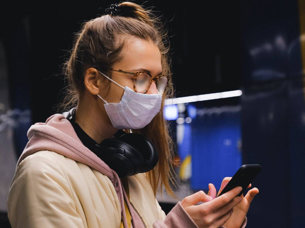 a woman on her phone with a mask on and foggy glasses