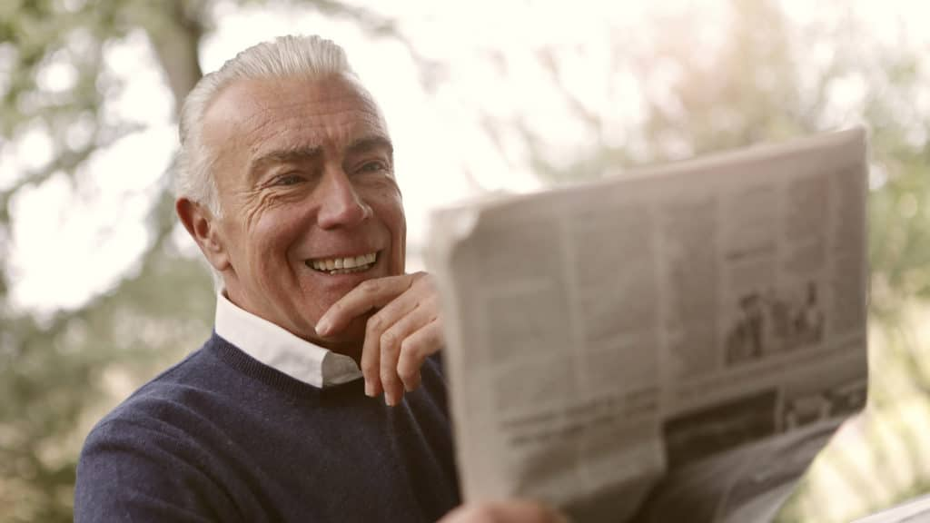 happy senior man reading without glasses with the Vivity IOL