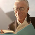 man with reading glasses and a book